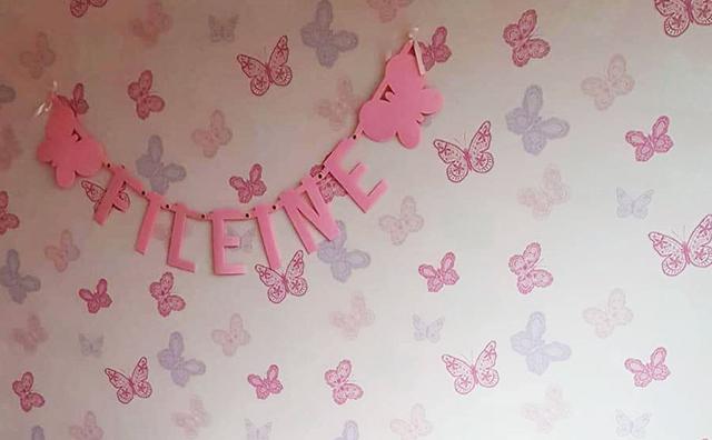 Roze vilten naamslinger voor baby Fileine met vlinders in de babykamer