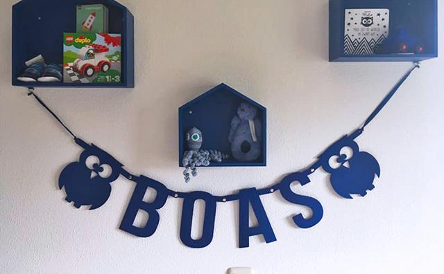 Blauwe vilten naamslinger voor baby Boas hangt in de babykamer