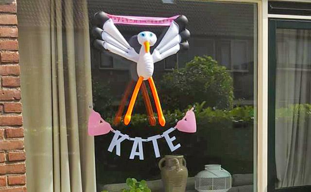 Vilten naamslinger en opblaasbare ooievaar voor het raam als aankondiging van de geboorte van baby Kate